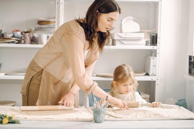 母と一緒に粘土を形作る少女の肖像画