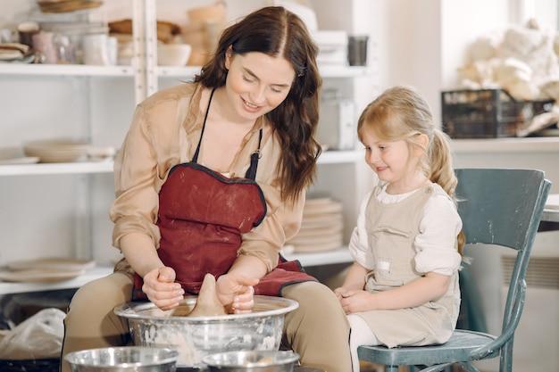 陶芸スタジオで娘と母が花瓶を作る