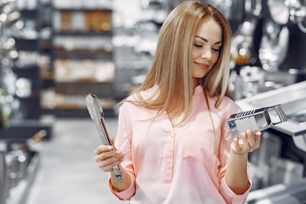 ピンクのブラウスを着た女性が店で料理を買う