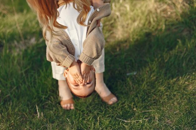 Мать с маленьким сыном, играя в летнем поле