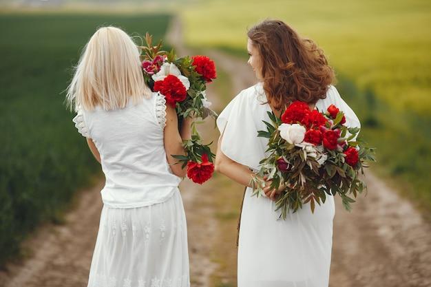 Женщины в элегантном платье стояли в летнем поле