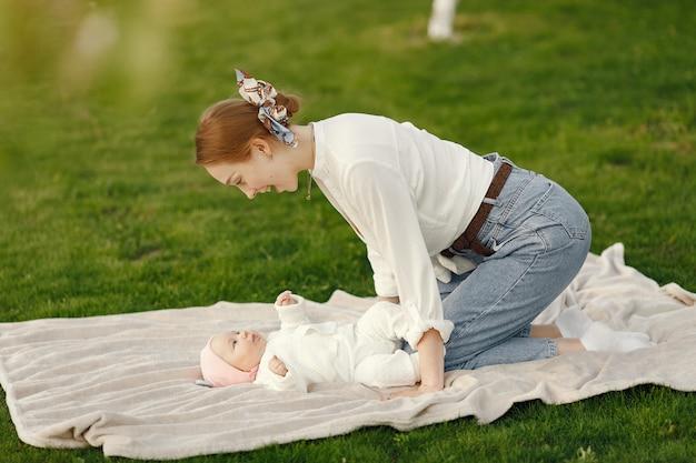 彼女の赤ちゃんと母親は夏の庭で時間を過ごす
