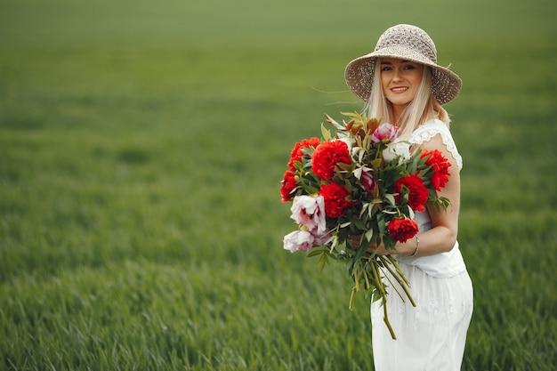 Женщина в элегантном платье, стоя в летнем поле