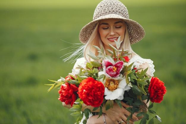 夏の畑に立っているエレガントなドレスを着た女性