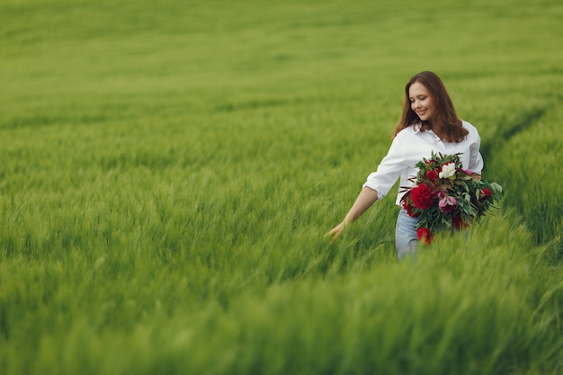 夏の畑で青いシャツの女性
