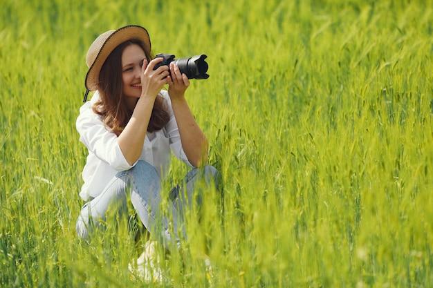 夏の畑で撮影する女性
