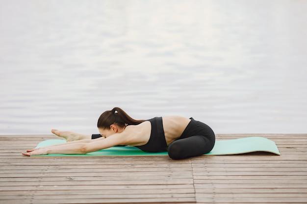 Женщина занимается йогой на воде