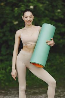 夏の公園で高度なヨガの練習の女性