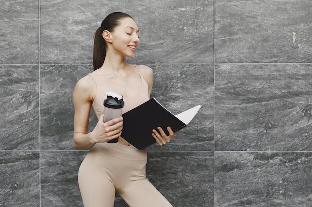 Женщина практикует передовые йоги против темной городской стены
