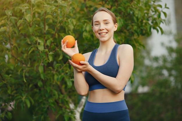Женщина в спортивной одежде держит фрукты