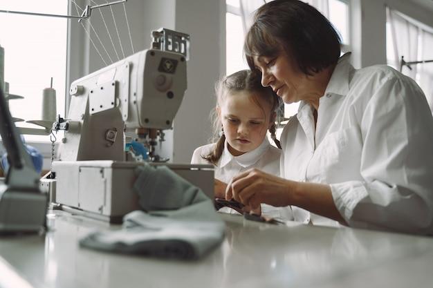 小さな孫娘とおばあちゃんが工場で服を縫う
