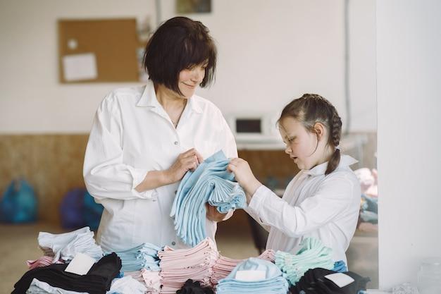 Бабушка с маленькой внучкой измеряют ткань для шитья