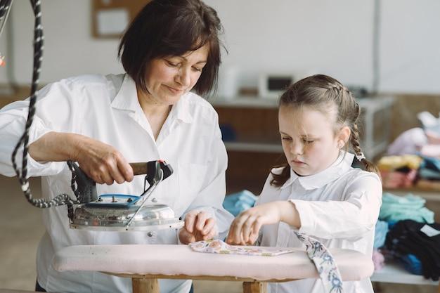 工場で小さな孫娘の鉄の服を着たおばあちゃん
