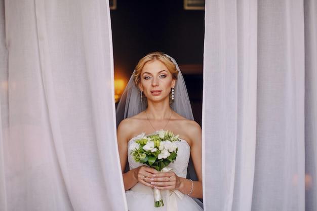 彼女の花束を示すブロンド花嫁