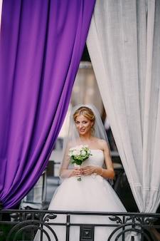カーテンの背景と彼女の花束を保持興奮花嫁