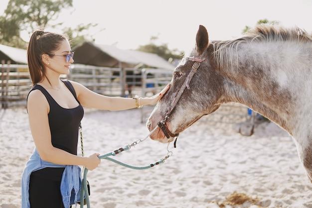 女の子、馬に乗る準備をする