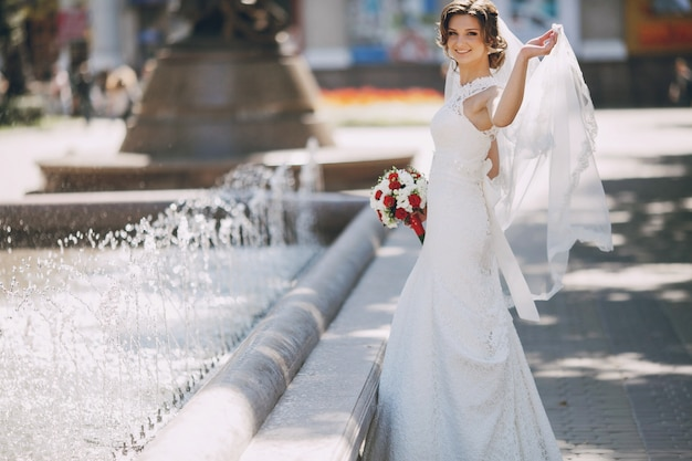 Радостный невеста держит вуаль с ее левой рукой