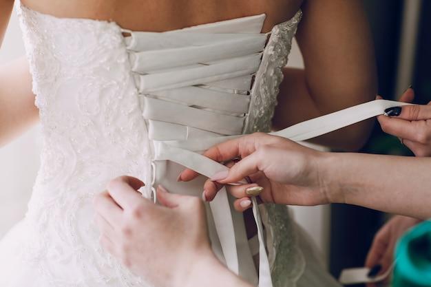 結婚式のコルセットを締める手