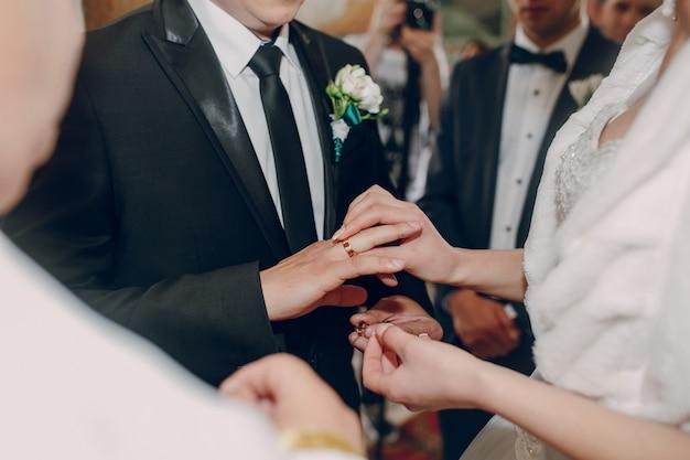 花嫁は彼女の夫にリングを置きます