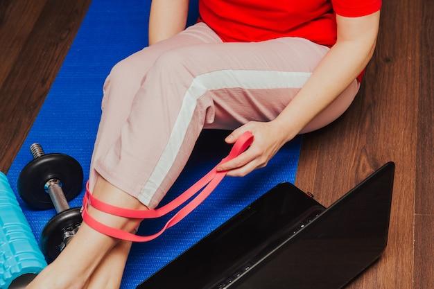 Женщина во время ее фитнес-тренировки дома с резиновой лентой сопротивления