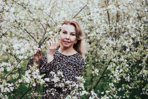ブルーミングガーデンの若い美しいブロンドの女性。