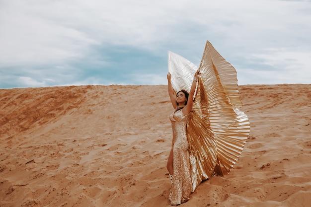 翼のある華麗なドレスと金色の美しい金髪の女性、スーツは砂の上の砂漠で東洋の東のダンスを踊っています。ベリーダンスの衣装を着た美しいエキゾチックな女性ダンサー。