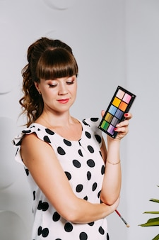 Визажист в работе. красочные тени в руке визажиста. косметический салон. концепция макияжа