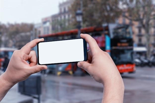 Макет смартфона в мужских руках на улице