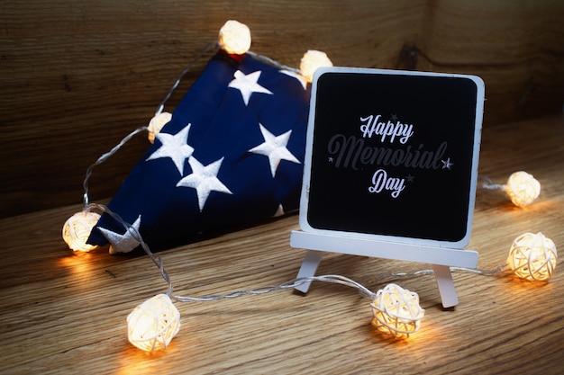 Американский флаг с гирляндой доски мела на деревянной предпосылке на день памяти погибших в войнах.