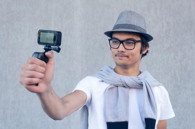 帽子とメガネの若いブロガーは、アクションカメラでビデオブログのビデオを撮影します。