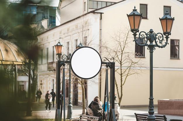 Круглый рекламный щит на улице с людьми.
