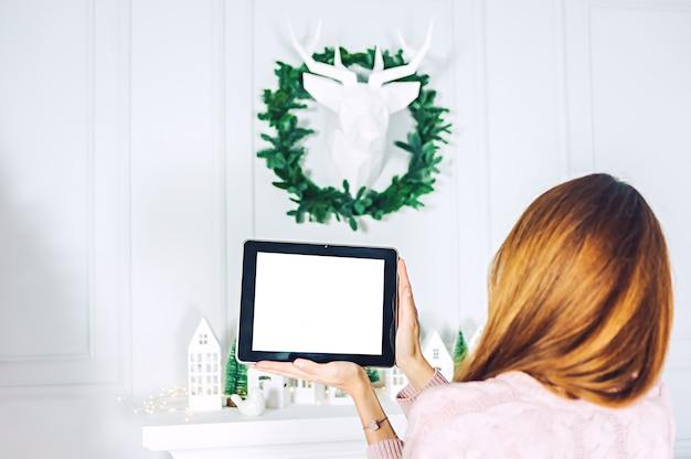 Макет планшета в руках девушки. на фоне стены с декоративным оленем и венком из праздничных домиков.