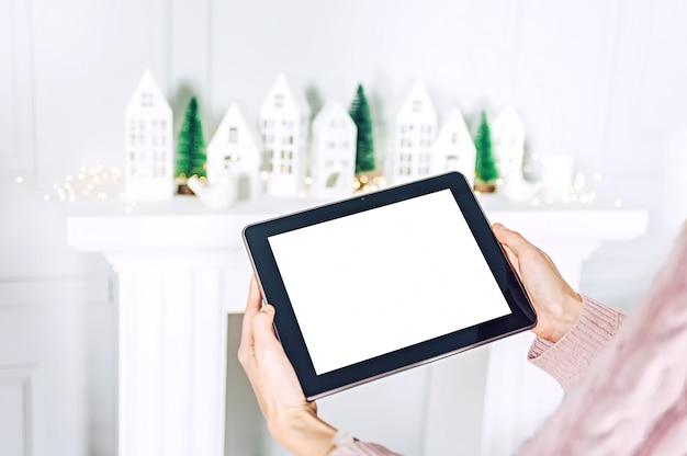 Макет планшета в руках девушки на фоне елки с декоративными домами праздничного украшения.