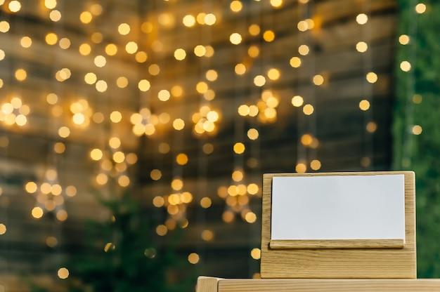 Пустой календарь - дневник на дубовой подставке белая карточка. против боке звезд гирлянды.