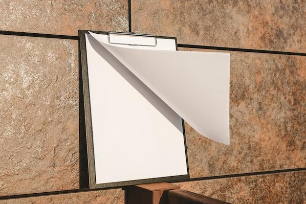 壁に紙のタブレットのモックアップ