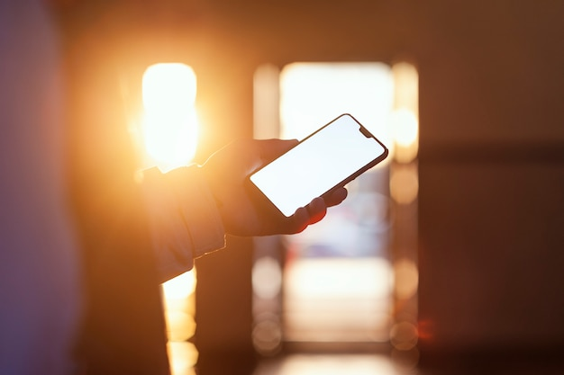 日没に対する人の手の中にあるスマートフォン。