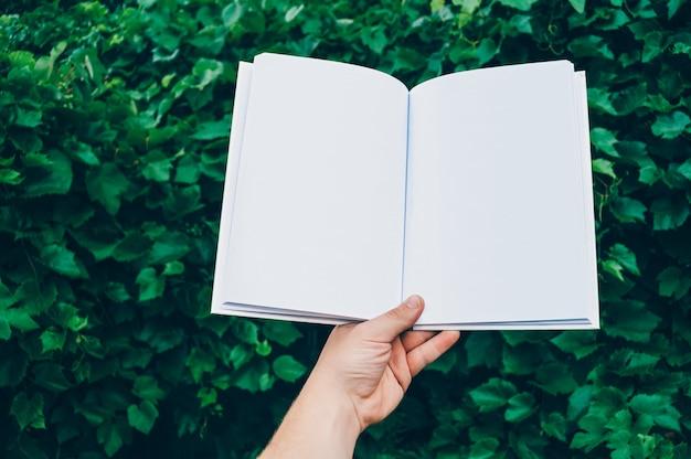 緑の葉を背景に、本の男の本。