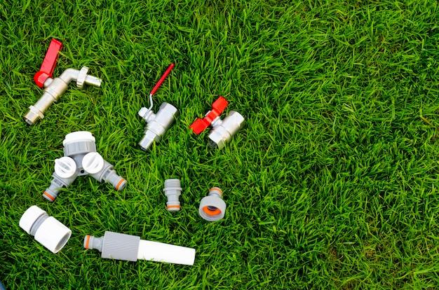 プラスチック、水まき缶、庭の水まき用のホース、芝生。