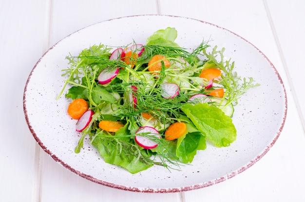 Свежие овощи и листья зеленых салатов на белой тарелке