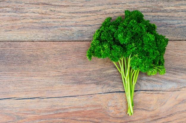 木製のテーブルに新鮮な緑のパセリの束