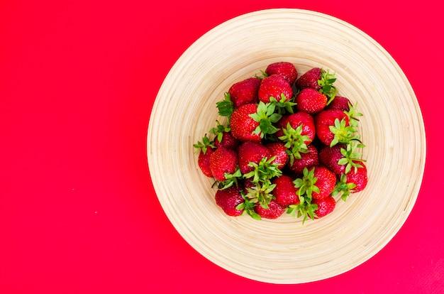 Спелая сладкая красная клубника на деревянной тарелке