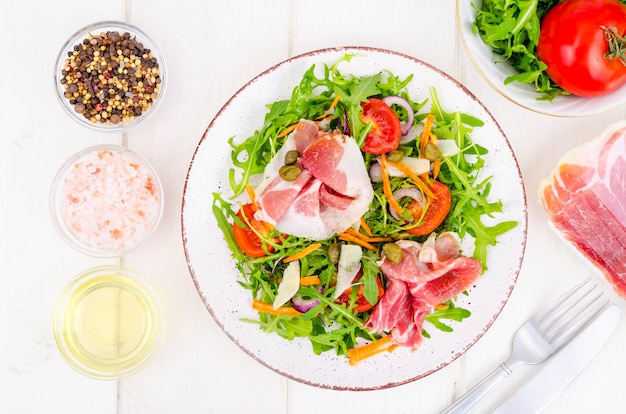 Свежий домашний салат с рукколой, хамоном, рукколой, помидорами, пармезаном.