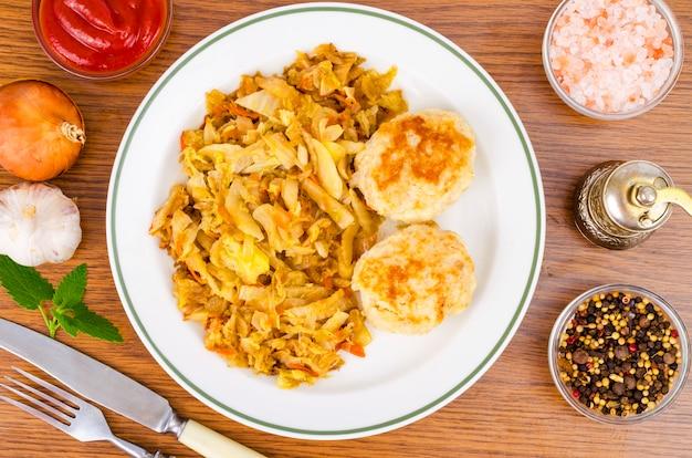 キャベツの煮込み、肉のカツレツ、スパイス、木製のテーブルの塩。