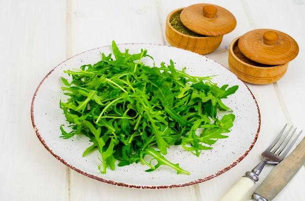 ベジタリアンフード。プレート、白い木製の新鮮な緑のルッコラ