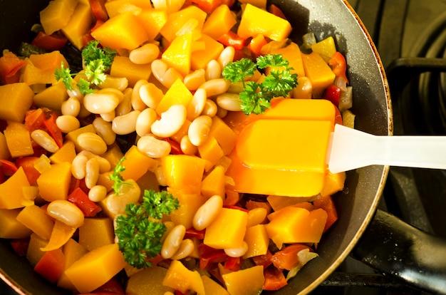 Овощное рагу с тыквой и белой фасолью в сковороде