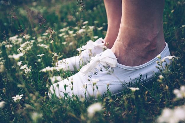 花と草原の上に立ってスニーカーの女性。