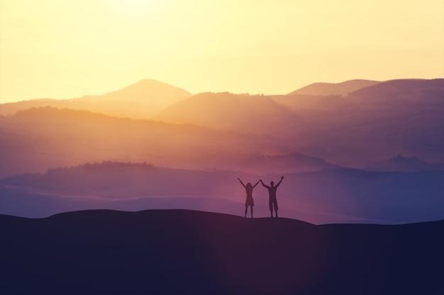 幸せな男と女、丘の上に立っています。