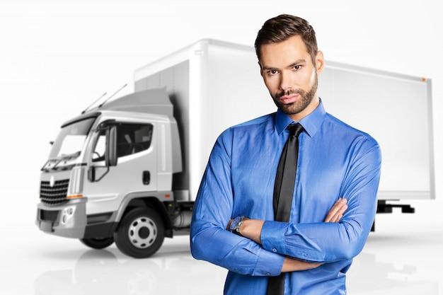 トラックの前に立っている実業家。