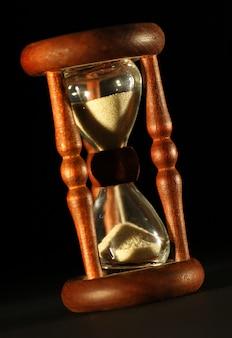 Крупным планом старинные песочные часы с черным фоном