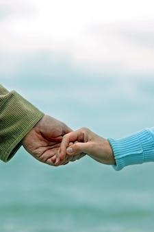 海をバックグラウンドで握手